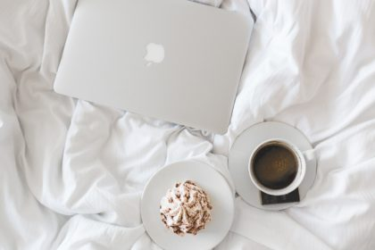 coffee and laptop on bed